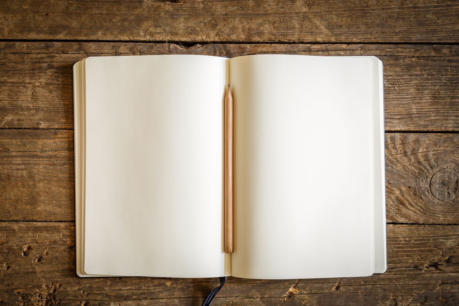 An empty notebook with a pencil down the crease on a wood table.