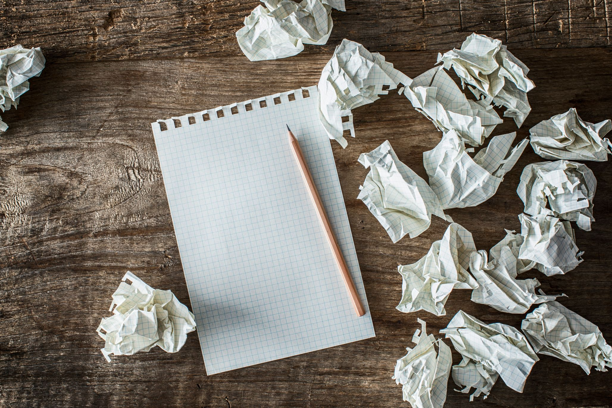 Notepad surrounded by crumpled up paper