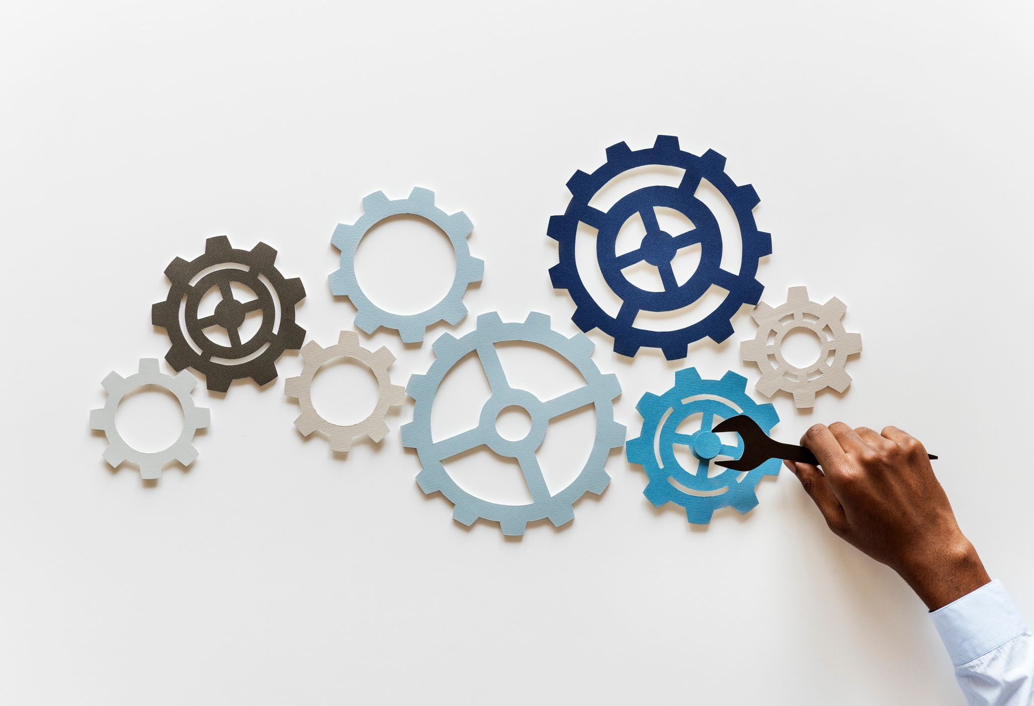 Photo of gears and a hand with a wrench turning them