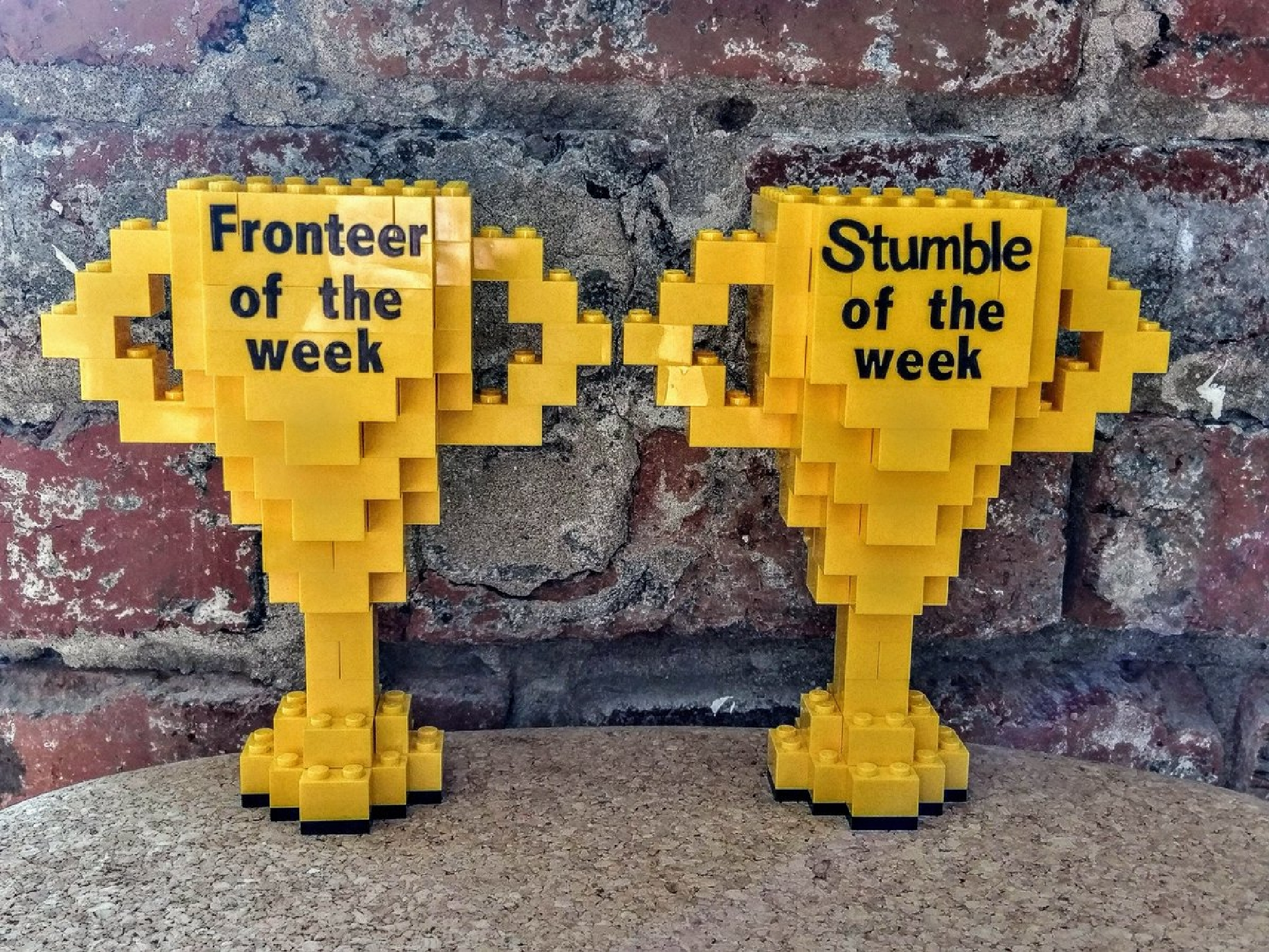 Fronteer of the Week and Stumble of the Week trophies crafted out of legos