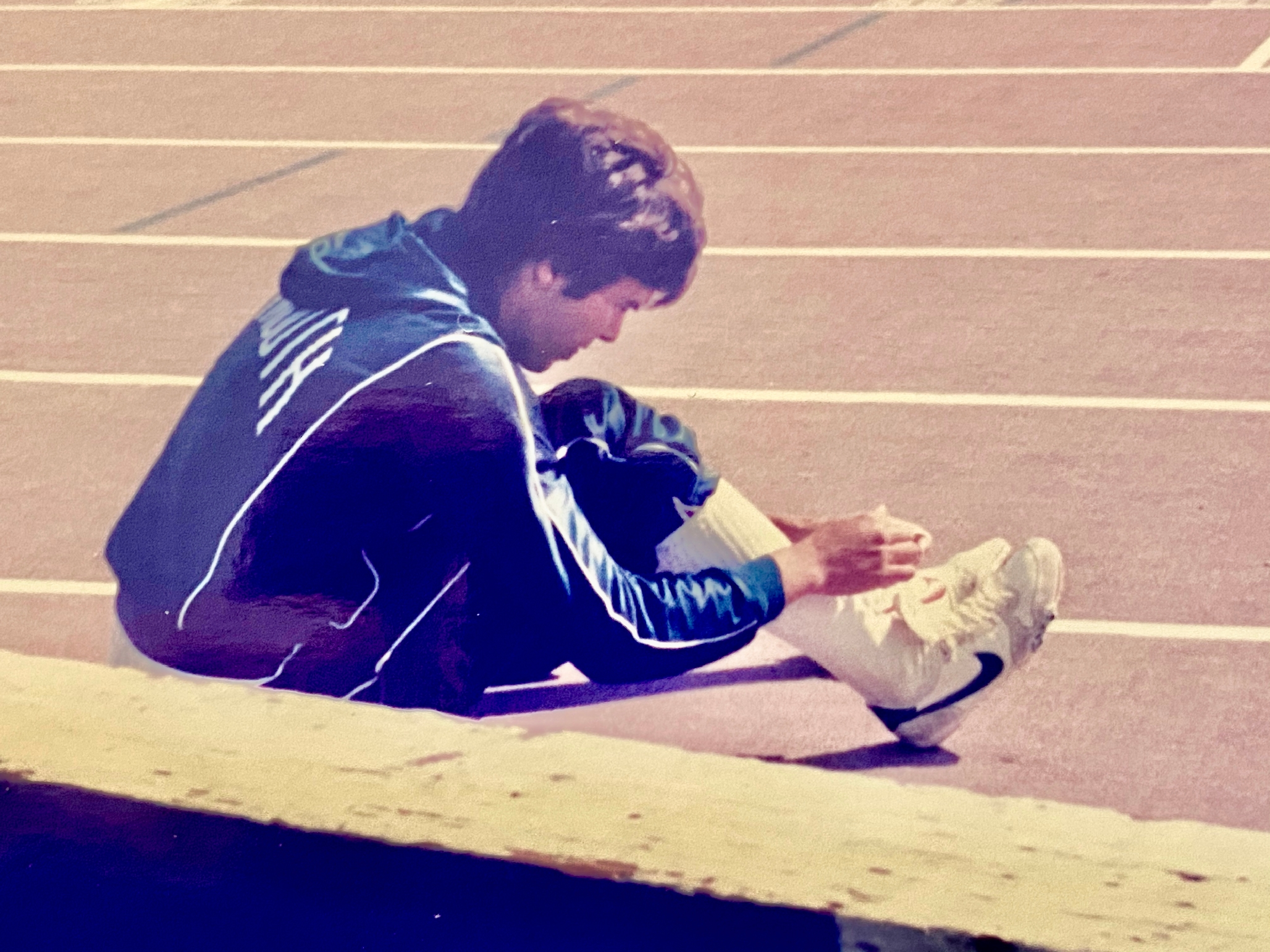 Photo of a young Dave Girouard, lacing up before a 400M race at Dartmouth.